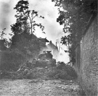 Infantry take cover behind Sherman tank during street fighting.
